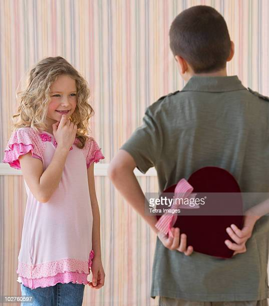 Young boy hiding a box of chocolates from young girl