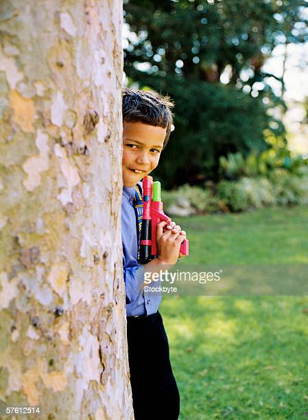 Young boy (4-8) hiding behind a tree holding a water gun