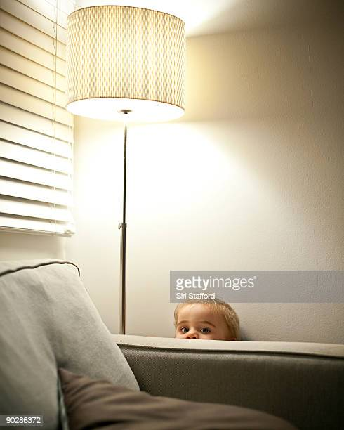 Young boy hiding behind couch, peeking over armres