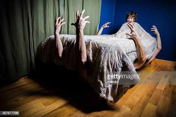 Young boy hiding in bed with monsters under bed