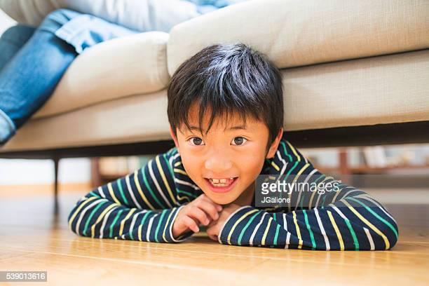 Junge versteckt unter dem sofa