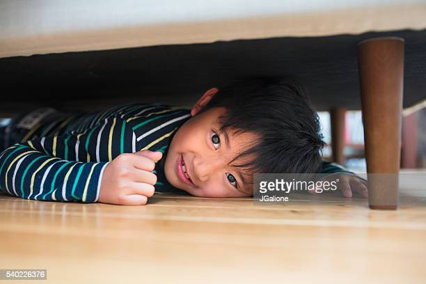 Young boy hiding under the sofa