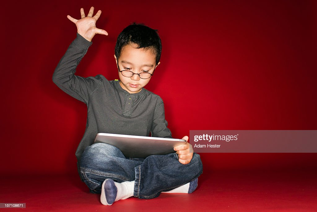 A young boy holding a tablet device inside. : Stock Photo