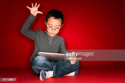 A young boy holding a tablet device inside. : Stockfoto