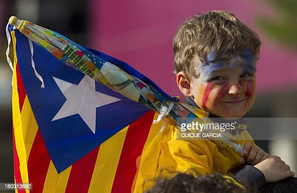 A young boy holding an Independentist Catalan flag smiles as Catalans gather in a bid to create a 400kilometre human chain part of a campaign for...
