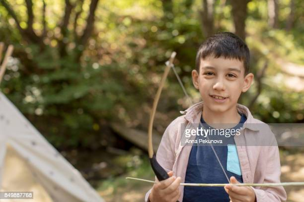 Young boy holding archery bow and an arrow