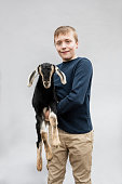 young boy holding baby goat