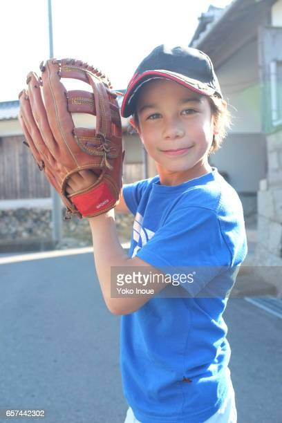 Young boy holding baseball glove in the street