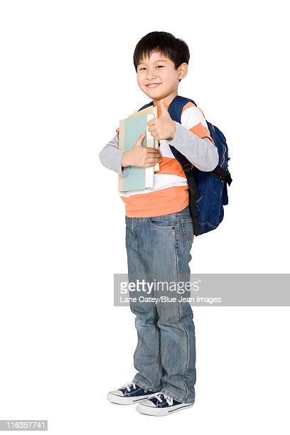 A young boy holding books and giving a thumbs up