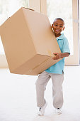 Young boy holding box in new home smiling