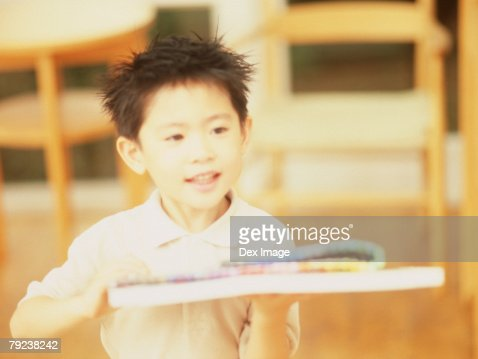 Young boy holding drawing materials : Stock Photo