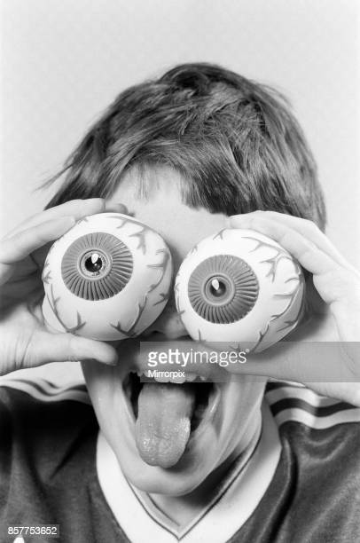 A young boy holding fake eye ball toys up to his eyes 21st October 1986