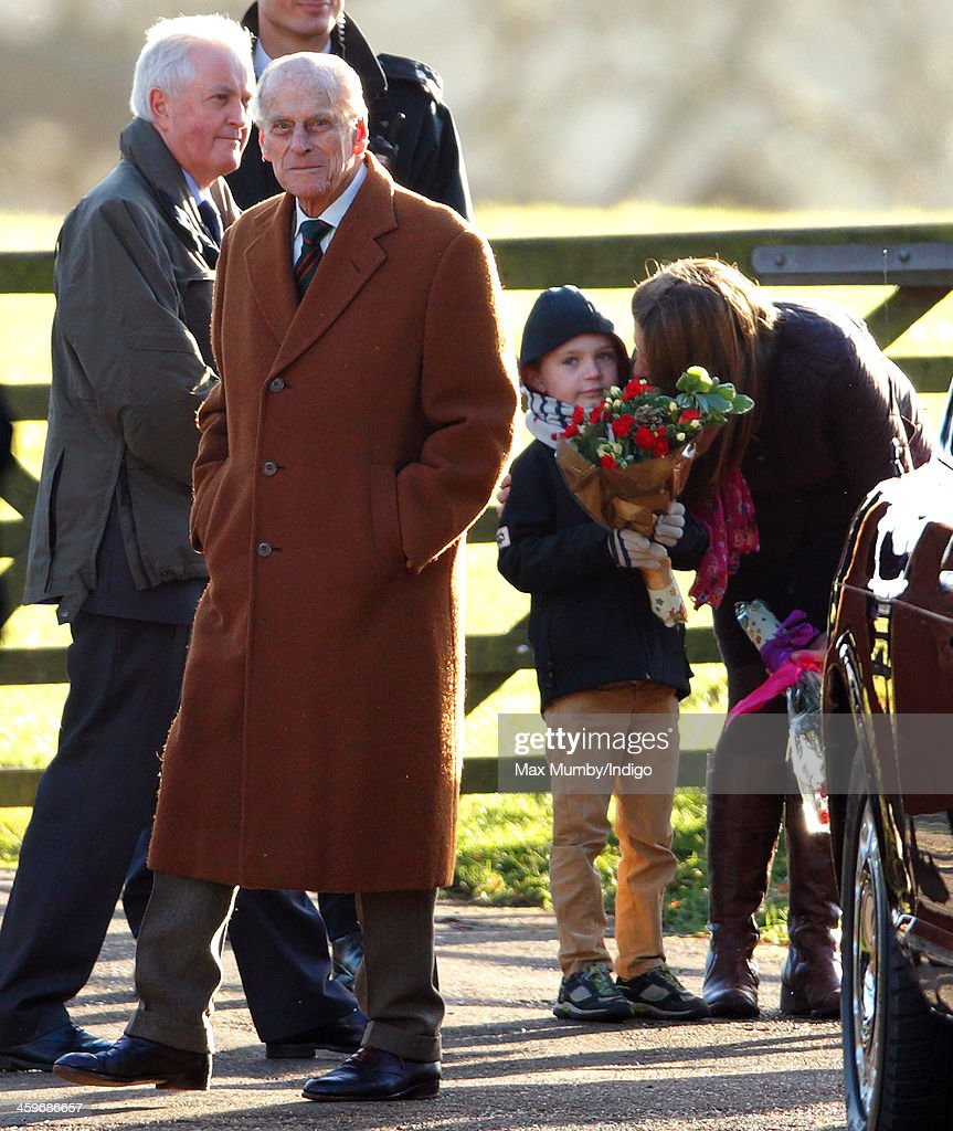 A young boy holding flowers looks on as <a gi-track='captionPersonalityLinkClicked' href=/galleries/search?phrase=Prince+Philip&family=editorial&specificpeople=92394 ng-click='$event.stopPropagation()'>Prince Philip</a>, Duke of Edinburgh leaves St. Mary Magdalene Church, Sandringham after attending Sunday service on December 29, 2013 near King's Lynn, England.