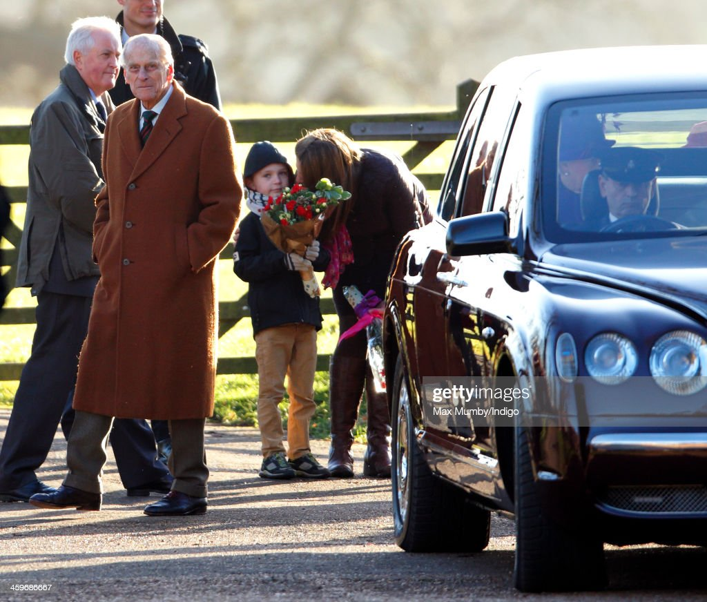 A young boy holding flowers looks on as <a gi-track='captionPersonalityLinkClicked' href=/galleries/search?phrase=Prince+Philip&family=editorial&specificpeople=92394 ng-click='$event.stopPropagation()'>Prince Philip</a>, Duke of Edinburgh and Queen <a gi-track='captionPersonalityLinkClicked' href=/galleries/search?phrase=Elizabeth+II&family=editorial&specificpeople=67226 ng-click='$event.stopPropagation()'>Elizabeth II</a> (sitting in her Bentley car) leave St. Mary Magdalene Church, Sandringham after attending Sunday service on December 29, 2013 near King's Lynn, England.