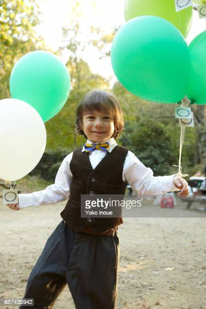 Young boy holding party balloons