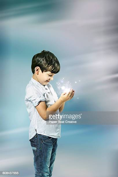 Young boy holding sparkles in his hand
