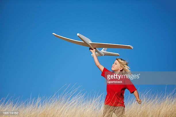 Young Boy Holding Toy Glider Airplane