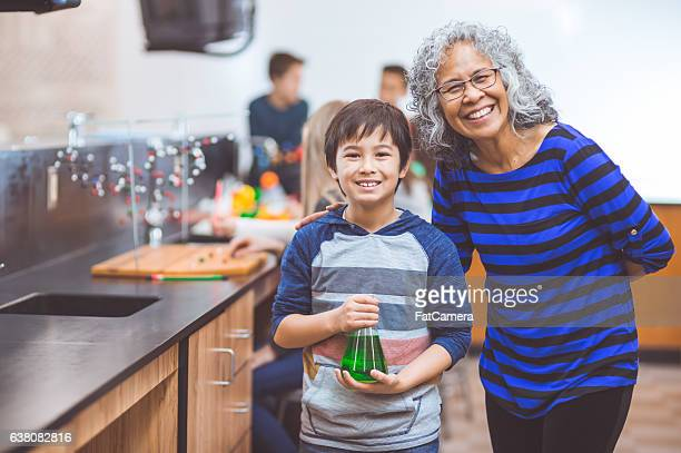Young boy holding up a science beaker doing STEM activities