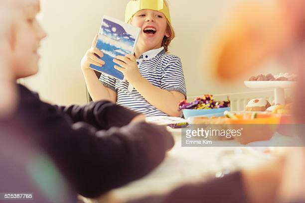 Young boy holding up opened Christmas present at table