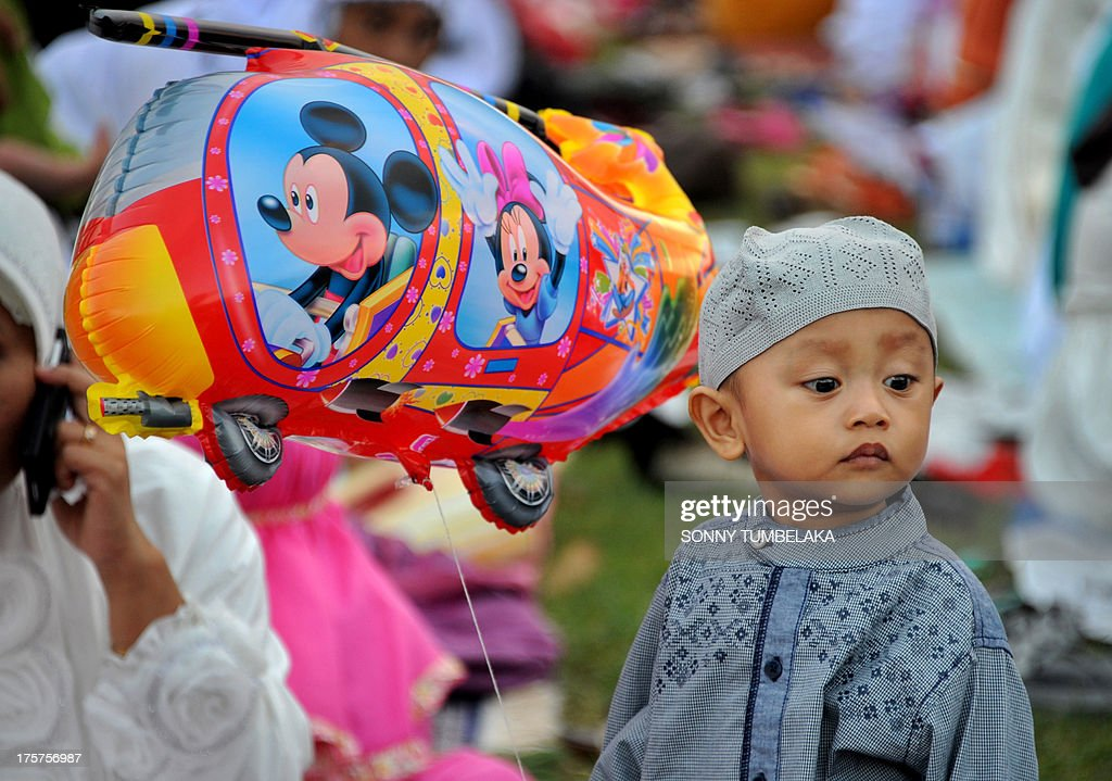 A young boy holds a balloon as Indonesian Muslims gather to take part in special morning prayers near the Bajrah Sandhi monument in Denpasar on Indonesia's island of Bali on August 8, 2013. Muslims around the world will celebrate Eid al-Fitr this week, marking the end of holiest month of Ramadan during which followers are required to abstain from food, drink and sex from dawn to dusk. AFP PHOTO / SONNY TUMBELAKA