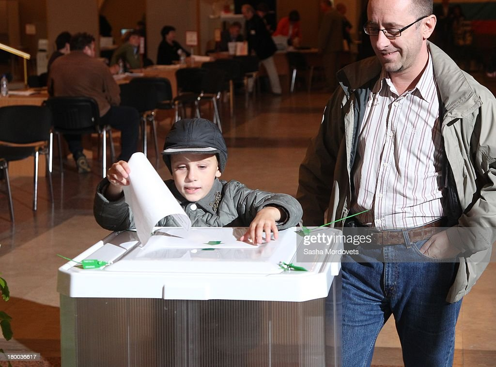 A young boy holds a ballot paper at a polling station for the mayoral elections on September 08, 2013 in Moscow, Russia. Opposition leader Alexey Navalny, one of Putin's most vocal critics is a candidate for mayor in Moscow.