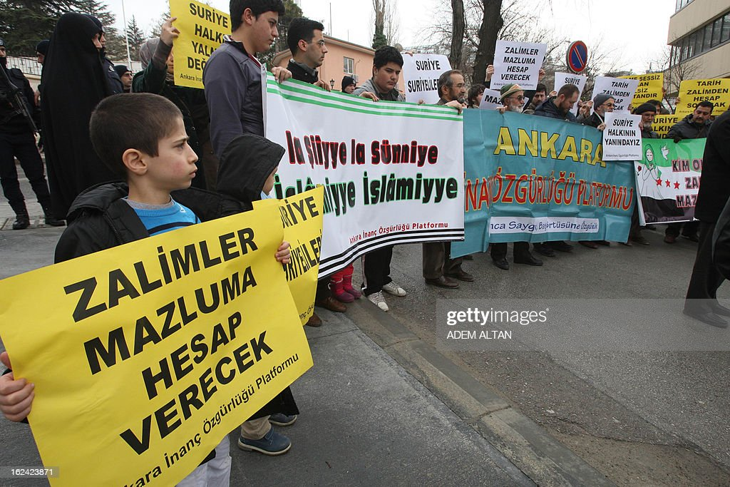 A young boy holds a banner that reads 'Syria belongs to Syrians' as members of an Islamic rights group stage a protest against Iran for its support to the Syrian regime, outside the Iranian embassy in Ankara, on February 23, 2013.