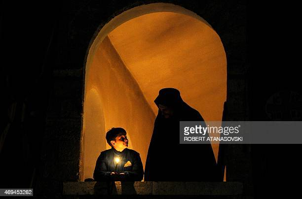 A young boy holds a candle as he speaks with an Orthodox priest during an Easter service at the Saint Jovan Bigorski monastery in Mavrovo some 115 km...