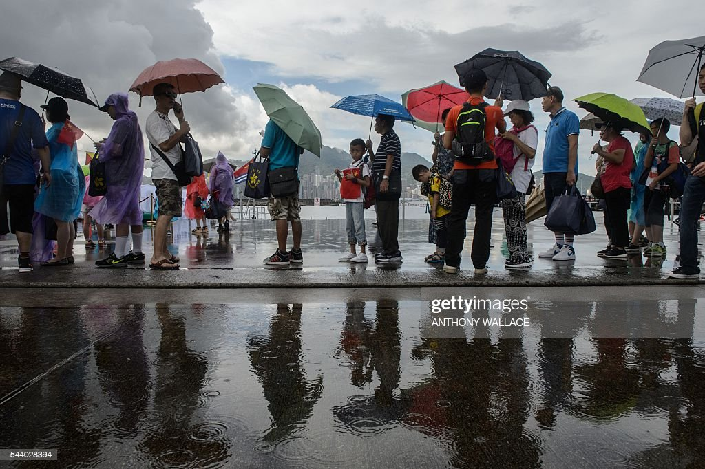 A young boy (C) holds a Chinese flag as he stands in a queue after heavy rain during the open day of the Chinese People's Liberation Army (PLA) Navy Base at Stonecutter Island in Hong Kong on July 1, 2016, to mark the 19th anniversary of the Hong Kong handover to China . / AFP / Anthony Wallace