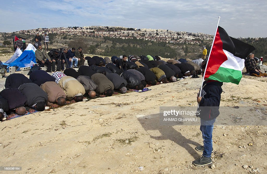 A young boy holds a flag as people pray during a protest of Palestinian activists over confiscated lands by Israeli army on January 25, 2013 in the West Bank village of Beit Iksa. Activists said recently that the Israeli army would confiscate over 500 dunams (124 acres, 50 hectares) of land by the village, located on the northwestern outskirts of Jerusalem. On the background is seen an Israeli settlement.