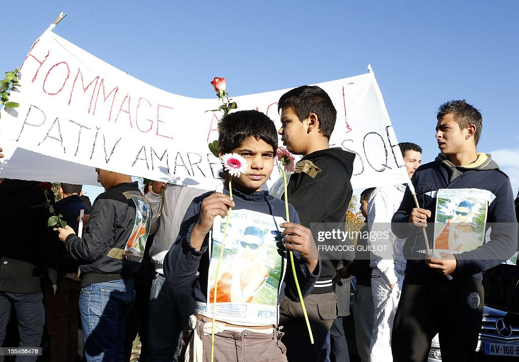 A young boy holds a flower and a portrait of one of the two Roma teenage boys hit by a car as they were riding on a bicycle on October 31, 2012 in Noisy-le-Grand, east of Paris, as he takes part in a silent march in their memory, on November 4 in Noisy-le-Grand. One of the two boys, aged 15, died and the other one, aged 12, was seriously injured.