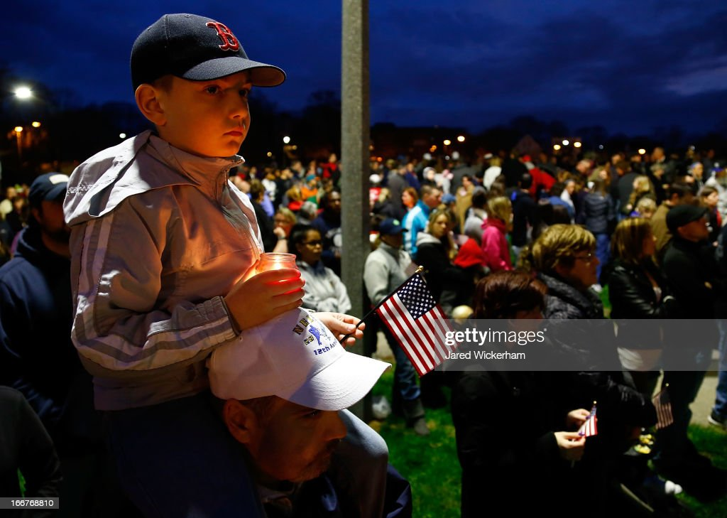 A young boy holds a lit candle and an American flag atop his father's shoulders during a vigil for eight-year-old Martin Richard, from Dorchester, who was killed by an explosion near the finish line of the Boston Marathon on April 16, 2013 at Garvey Park in Boston, Massachusetts. The twin bombings resulted in the deaths of three people and hospitalized at least 128. The bombings at the 116-year-old Boston race resulted in heightened security across the nation with cancellations of many professional sporting events as authorities search for a motive to the violence.