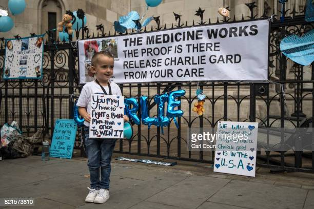A young boy holds a placard given to him by his mother as supporters of of terminally ill baby Charlie Gard protest outside the High Court after the...
