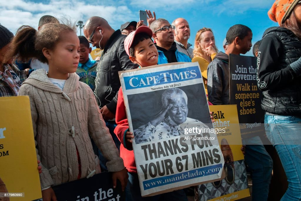 TOPSHOT - A young boy holds a poster with a photo of former South African President and Nobel Peace Prize laureate, Nelson Mandela, during Mandela Day, commemorating Mandela's birthday and his initiative against poverty, on July 18, 2017 in Cape Town, within a march during the Walk Together campaign of The Elders group. The Elders, an independent group of global leaders working together for peace and human rights, mark their 10th birthday by launching 'Walk Together', a global campaign to help bridge the global faultlines of division, hate and xenophobia. Mandela Day initially urged individuals to spend 67 minutes on 18 July on community service. /