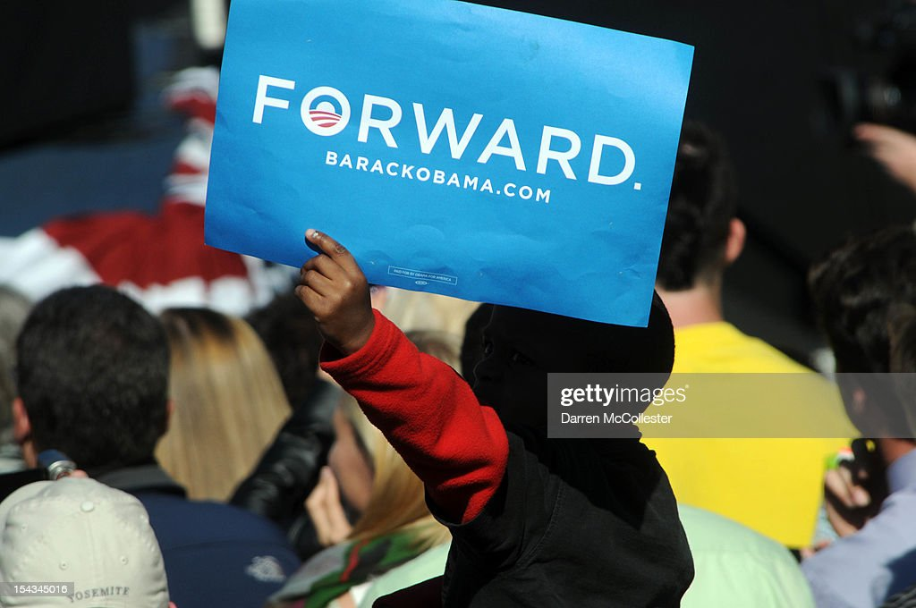 A young boy holds a sign as President Barack Obama speaks at an event at Veteran's Memorial Park October 18, 2012 in Manchester, New Hampshire. President Obama continues to campaign in swing states with just under three weeks left till Election Day.