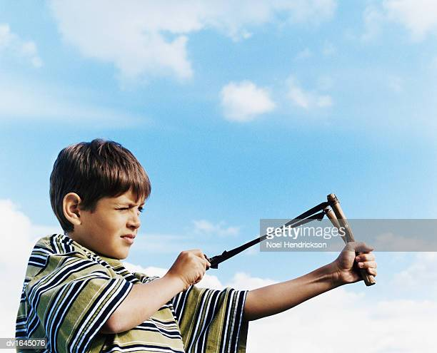 Young Boy Holds a Slingshot and Aims With it, Looking Ahead