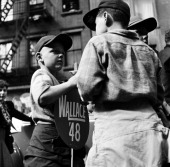 A young boy holds an ice cream on a stick in one hand and a campaign sign for Progressive Party candidate Henry Wallace at an outdoor event Brooklyn...