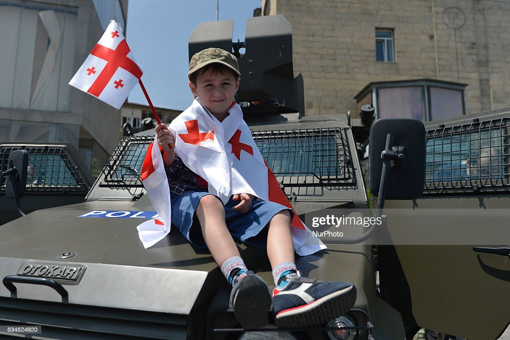 A young boy holds the flag of Georgia and seats on the Police car in Tbilisi center, as many people gathered in Georgian capital for a popular celebrations. Georgia celebrates today its Independence Day commemorating the adoption of the Act of Independence in 1918, that outlined the main principles of the nation's democratic development and formed a first-ever republic under German and British protection, but was then invaded by Bolshevik Russia and absorbed into the Soviet Union. On April 9, 1991, Georgia once again regained its independence. This year Georgia celebrates the 25th Anniversary since the restoration of its independence. Tbilisi, Georgia, on Thursday 26 May 2016.