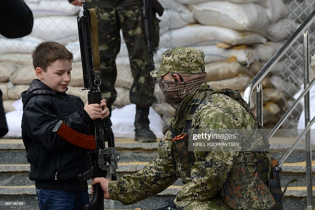 A young boy holds the machine gun of an armed man in military fatigue guarding a barricade outside the regional administration building in the eastern Ukrainian city of Slavyansk on April 20, 2014. Pro-Moscow rebels in Slavyansk declared a curfew there Sunday, after a gun battle with unidentified attackers killed two militants. Separatist rebels leader Vyacheslav Ponomaryov told reporters that 'the curfew comes into effect today'. AFP PHOTO / KIRILL KUDRYAVTSEV