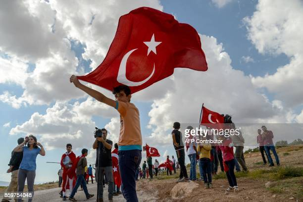 A young boy holds up a Turkish national flag during a demonstration in support of the Turkish army's Idlib operation near the TurkeySyria border near...