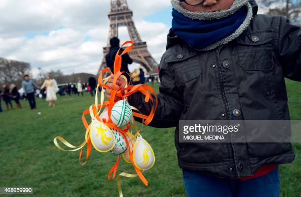 A young boy holds up eggs during an Easter egg hunt organized by the French nonprofit organization 'Secours populaire' at the Champ de Mars in front...