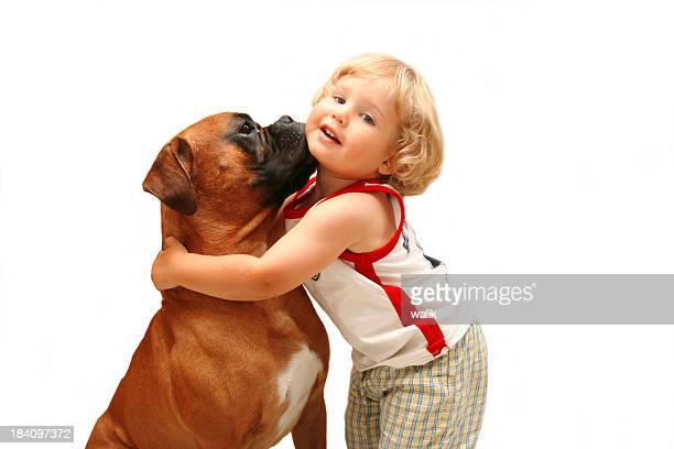 Young boy hugging a boxer on white background