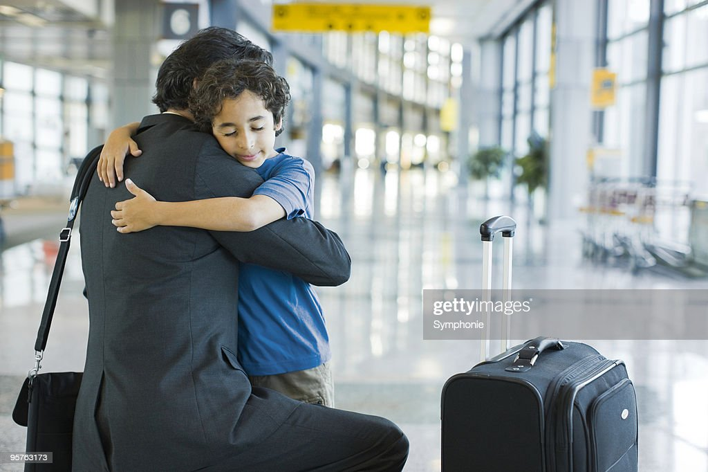 Young boy hugging father in airport terminal : Stock Photo