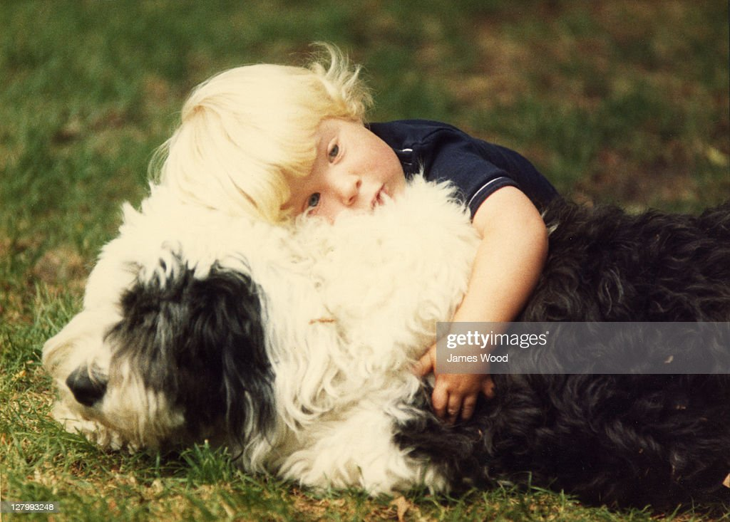 Young boy hugging Old English Sheepdog : Stock Photo