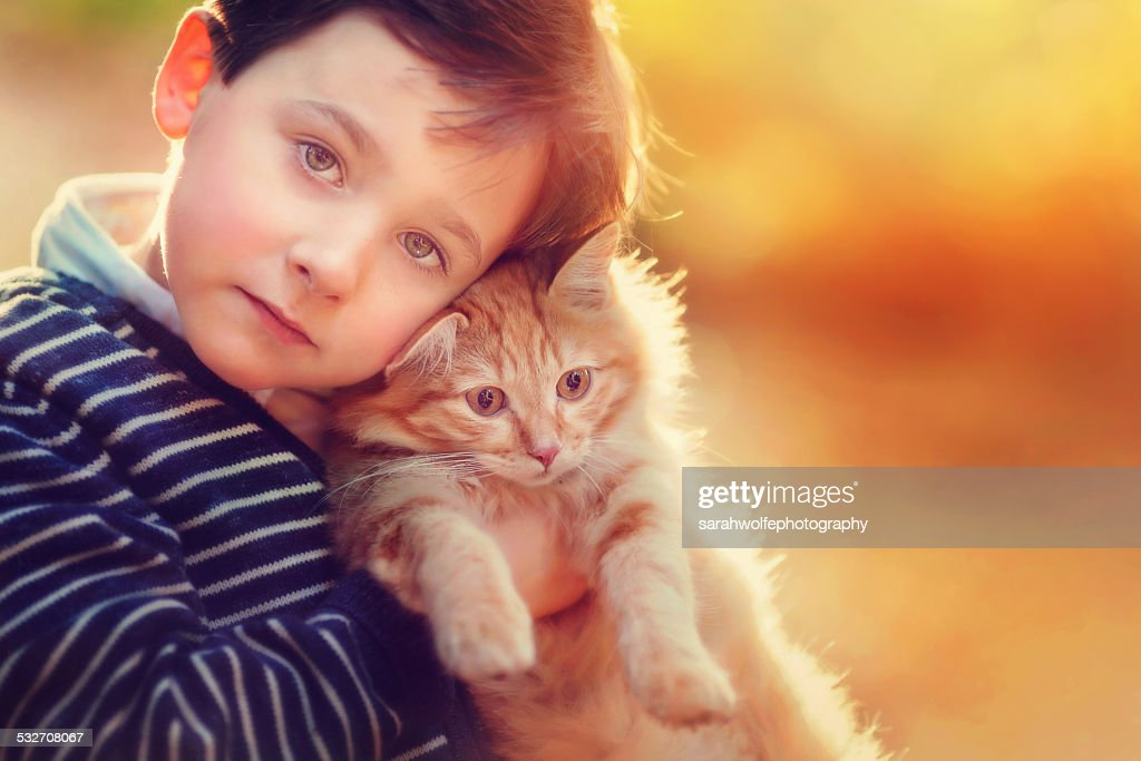 young boy hugging orange cat