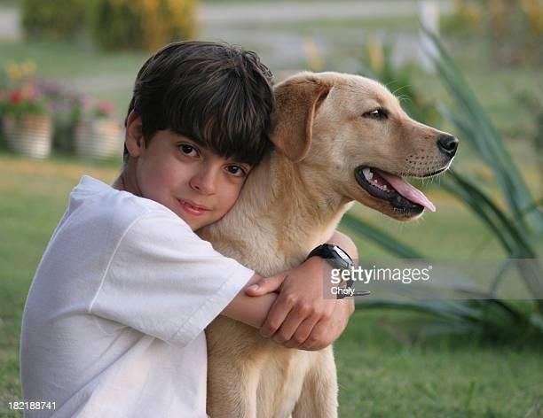 Young boy hugs his yellow Laborador dog outside