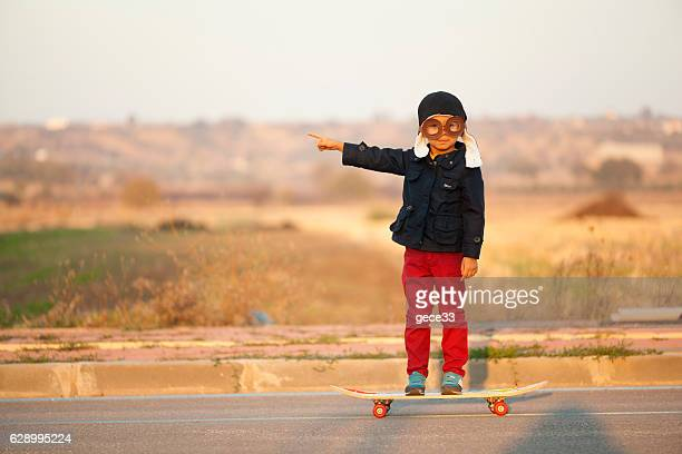 Young Boy Imagines with pilot helmet On Skateboard