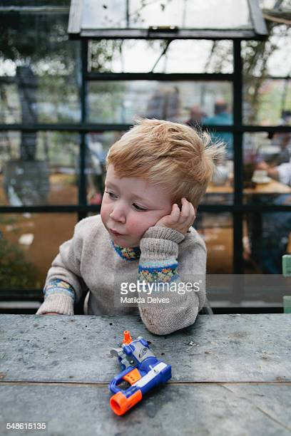 Young boy in a cafe looking unhappy