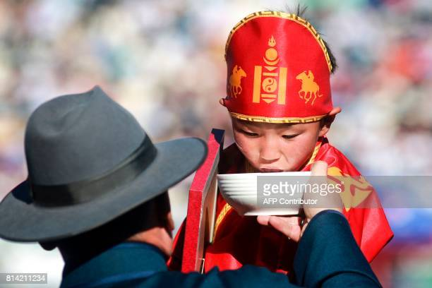 A young boy in a costume drinks milk during the traditional Nadaam festival in Ulan Bator on July 12 2017 The festivities consist of a number of...