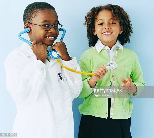 Young Boy in a Doctor Costume and Young Girl Playing With a Stethoscope