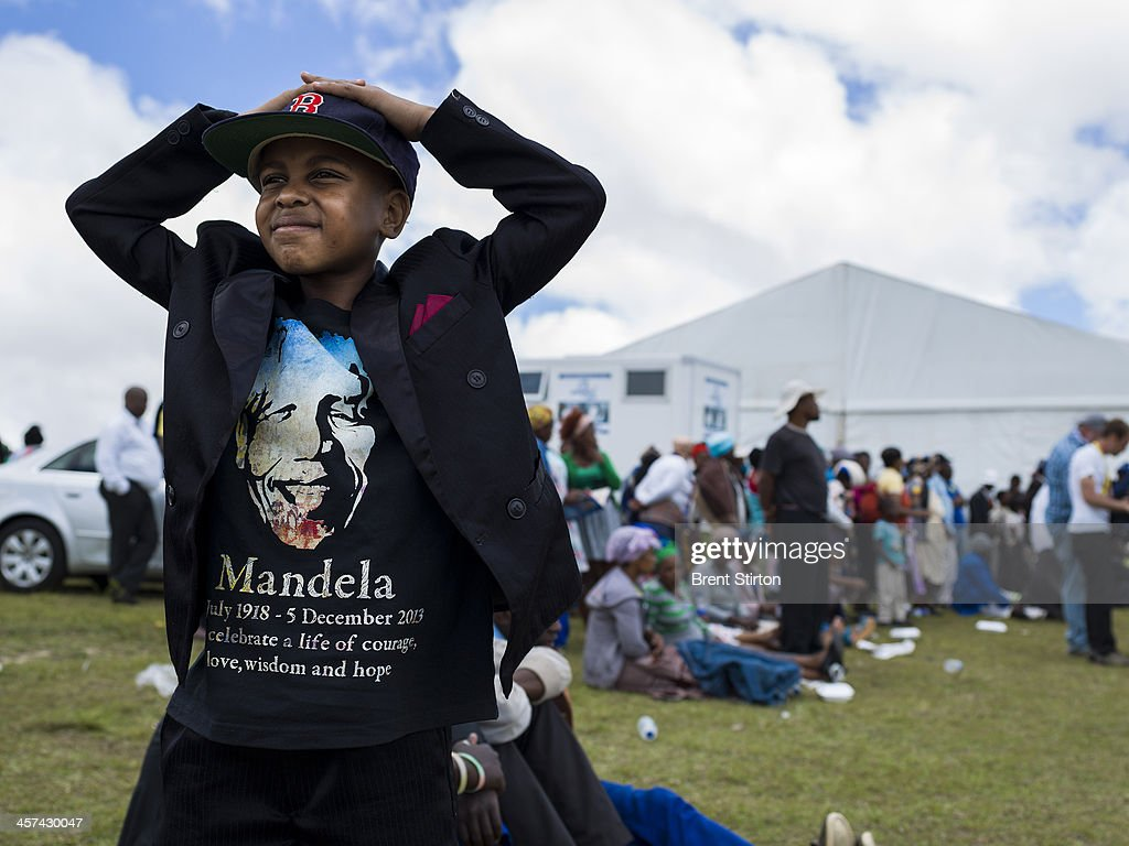 A young boy in a Nelson Mandela T Shirt watches Mandela's funeral on a jumbo television broadcasting the service taking place in the valley below, Qunu, South Africa, 14 December 2014. An icon of democracy, Mandela was buried at his family home in Qunu after passing away on the 5th December 2013.